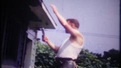 3021 home owner climbs ladder, paints his house - vintage film home movie Stock Footage