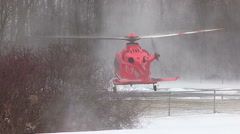 Air ambulance lifts off with car accident victim in snowstorm Stock Footage