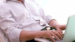 Man using laptop on sun lounger Stock Footage