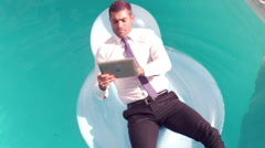 Stock Video Footage of Businessman using tablet pc on inflatable