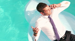 Businessman having a phone call on inflatable Stock Footage