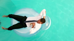 Stock Video Footage of Businessman drinking beer on inflatable