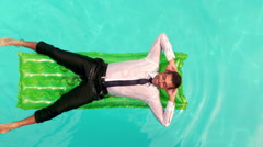 Stock Video Footage of Wet businessman relaxing on inflatable
