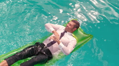 Stock Video Footage of Wet smiling businessman splashing on inflatable