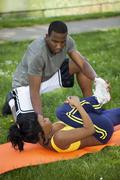 Black Woman Stretching On Orange Pad With Man - stock photo