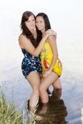 Two Women Standing In Water With Dresses - stock photo