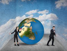 Stock Photo of Businessman pulls world sphere