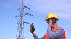 Electrical engineer on field inspecting electricity pillar on tablet and talking Stock Footage