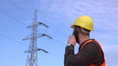 Foreman discussing technical issues with team concerning electricity pillar 4K Stock Footage