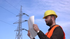Wire industry architect checking design plan for electricity pillar for faults Stock Footage