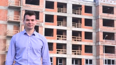 Male engineer in front of new apartment building block giving the thumbs up 4K Stock Footage