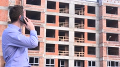 Stock Video Footage of Young real estate developer talking on mobile phone to material suppliers 4K