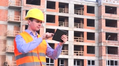 Foreman on residential apartment building site using tablet to check progress 4K Stock Footage