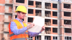 Architect on construction site checking building plan, blueprints, draw Stock Footage
