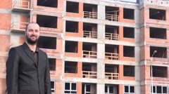 Successful young real estate developer outside apartment building portrait smile - stock footage