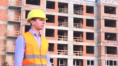 Architect with hard hat and vest in front of construction site drinking water 4K Stock Footage