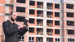 Stock Video Footage of Real estate developer in front of construction site checking tablet thumbs up 4K