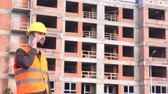 Stock Video Footage of Architect outside apartment building talking smartphone to real estate developer