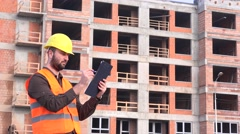 Engineering architect making notes on clipboard related to construction site 4K - stock footage