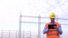 Stock Video Footage of Power grid supervisor checking electrical tension on tablet, high voltages 4K