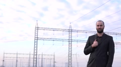 Young handsome businessman electrical industry hand in jacket, suit, power grid - stock footage