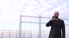 Stock Video Footage of Business person in energetic industry talking mobile phone in front of grid 4K