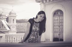 Classy attractive brunette wearing black white dress standing on city balcony - stock photo