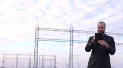 Business person in front of electrical power lines using tablet checking voltage - stock footage