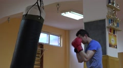 Amateur boxer practicing with punching bag, hooks, uppercuts, red boxing gloves Stock Footage
