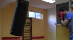Amateur boxer punching the bag hard, fists, defense, sportive guy at gym, manly  Stock Footage