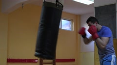 Stock Video Footage of Young man making sport indoor, aggressive athlete punching the bag, masculine 4K
