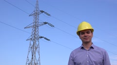Young electrical engineer smiling in front of electricity pillar, maintenance 4K Stock Footage