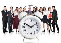 Business people stand near big alarm clock Stock Photos