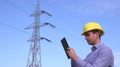 Inspection engineer verifying voltage of electricity poll using tablet, helmet Stock Footage