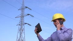 Busy foreman near electrical pillar talking on mobile phone and checking tablet  Stock Footage