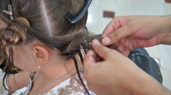 Hairdresser hands weaving a dreadlocks for girl Stock Footage