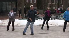 Senior citizens doing Tai Chi Chinese fitness on university campus Stock Footage