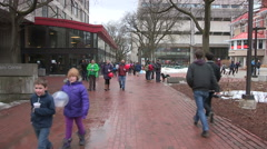 Students walking to class on campus with light snow flurries - stock footage