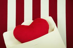 Valentines day background with heart in envelop on red and white striped fabr - stock photo