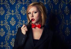 Young blonde with red lips and smoking pipe dressed in a men's suit Stock Photos