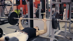 Man doing bench press workout in gym slow motion Stock Footage