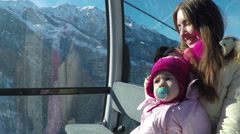 young mother with her little daughter riding on cableway in the mountains on a - stock footage