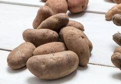 Potatoes on white wooden board Concept - stock photo