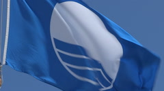 Blue flag flying at beach indicating clean water Stock Footage