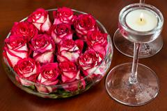 Red rosebuds in glass vase with water on wooden table with lit candle. Valent - stock photo