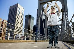 Stock Photo of Boy with gadget on the bridge in the city of skyscrapers