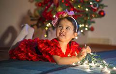 Adorable little girl playing with Christmas lights Stock Photos