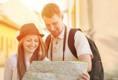 Stock Photo of Touristic couple looking at map on the city street