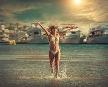 Stock Photo of Happiness female running on the beach, yachts background and und