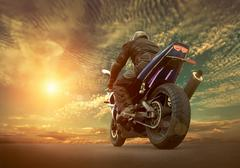 Man seat on the motorcycle under sky with clouds - stock photo